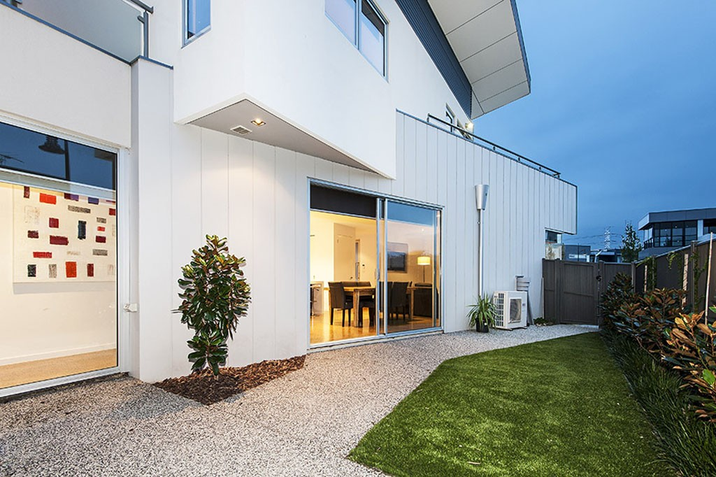 Large White Luxurry Home with overhanging sotrey and backyard