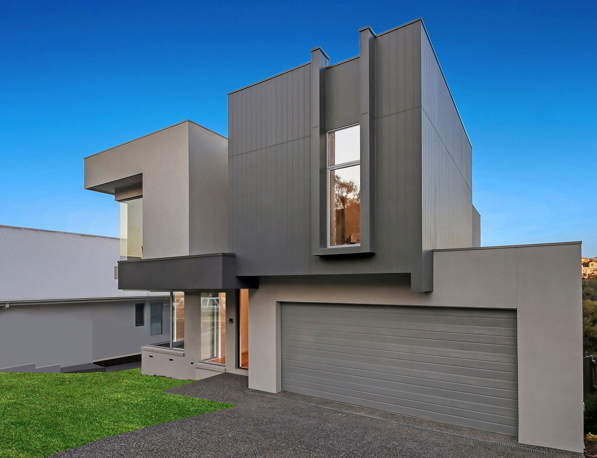 custom new home with modern facade, garage and front grass area