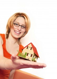 Woman holding small house in her hand