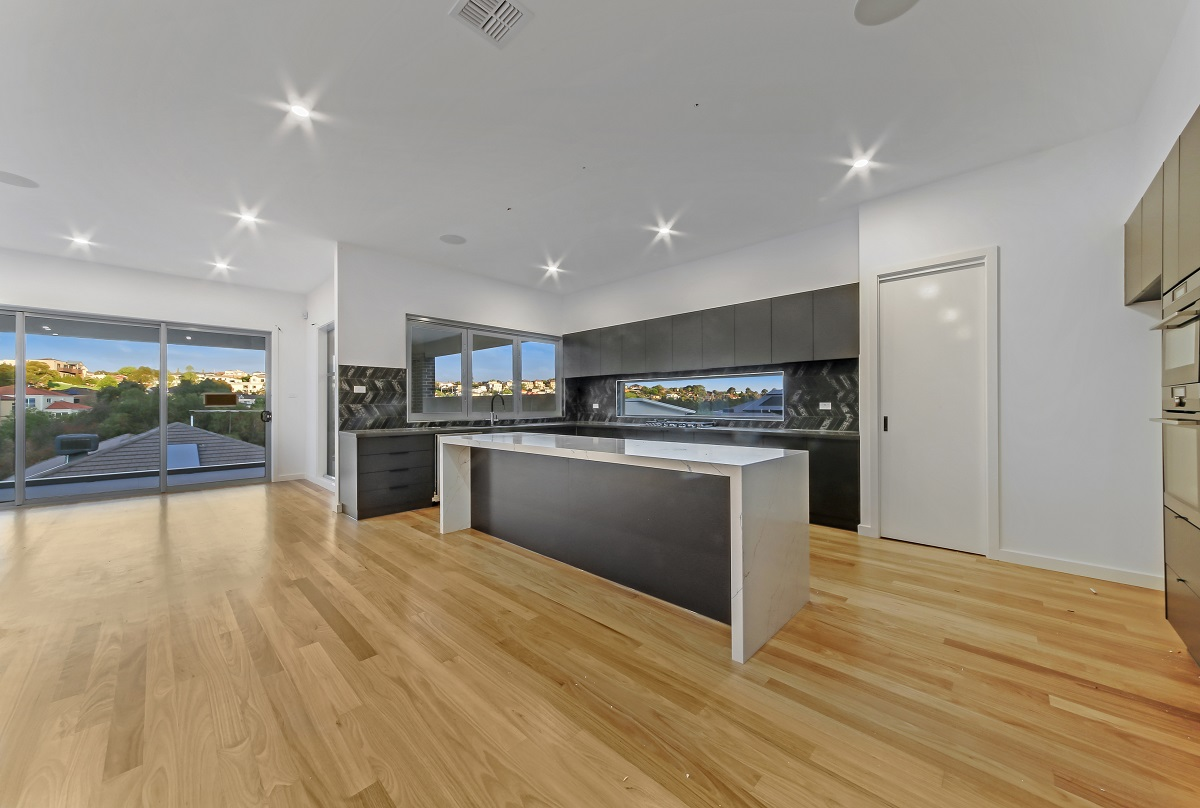 new home showing kitchen design with floor boards and centre bench