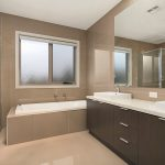 Modern bathroom in light beige colour scheme, bath, clear shower recess and double vanity in dark wood