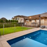 Backyard with grass area and pool, outdoor under cover entertaining with kitchen, glass double doors to house