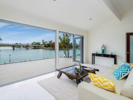 lounge area with large glazed window and sliding door overlooking lake