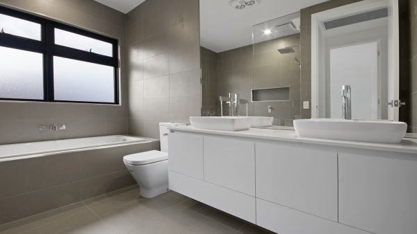 New bathroom with white vanity toilet and back in background with privacy glazing windows